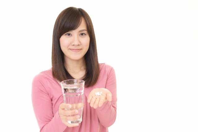 サプリを飲む女性